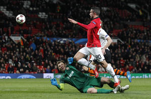 Photo - Manchester United's Robin van Persie, No 20, attempts a shot on goal as Donetsk's goalkeeper Andriy Pyatov dives to block during their Champions League group A soccer match between Manchester United and Shakhtar Donetsk at Old Trafford Stadium, Manchester, England, Tuesday, Dec. 10, 2013. (AP Photo/Jon Super)