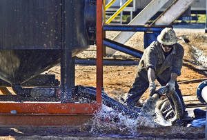 photo - Above and Right: Employees work Oct. 19 on a Continental Resources rig site in Chickasha.  Photos by Chris Landsberger, The Oklahoman