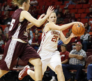 Photo - OU's Whitney Hand (25) passes around Roz Hamilton (35) of Oklahoma Christian during a women's' college basketball exhibition game between the University of Oklahoma and Oklahoma Christian University at the Lloyd Noble Center in Norman, Okla., Thursday, Nov. 1, 2012. Photo by Nate Billings, The Oklahoman