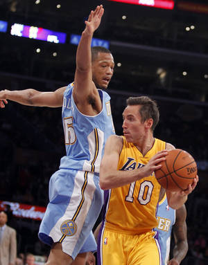 Photo - Los Angeles Lakers guard Steve Nash (10) looks to make a pass with Denver Nuggets forward Anthony Randolph defending during an NBA preseason basketball game Sunday, Oct. 6, 2013 in Los Angeles. (AP Photo/Alex Gallardo)