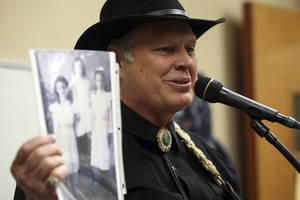 photo - Storyteller and musician Austin Ladd Roberts shows a photograph of his grandmother as he performs for special ed students at the San Antonio LIghthouse for the Blind, Tuesday, Nov. 27, 2012 in San Antonio, Texas. Roberts is part of a traveling troupe of singers and storytellers deployed by the Texas Heritage Music Foundation based in Kerrville.  (AP Photo/The San Antonio Express-News, Jerry Lara)  RUMBO DE SAN ANTONIO OUT; NO SALES