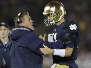 Photo -   Notre Dame head coach Brian Kelly talks to quarterbackTommy Rees, right, during the second half of an NCAA college football game against Michigan, Saturday, Sept. 22, 2012, in South Bend, Ind. Notre Dame defeated Michigan 13-6. (AP Photo/Darron Cummings)