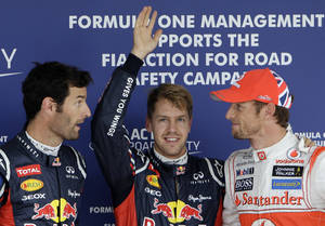 Photo -   Red Bull driver Sebastian Vettel of Germany, center, celebrates after taking pole position in qualifying for the Japanese Formula One Grand Prix, as second placed Red Bull driver Mark Webber of Australia, left, and third placed McLaren driver Jenson Button of Britain chat, at the Suzuka Circuit in Suzuka, Japan, Saturday, Oct. 6, 2012. (AP Photo/Greg Baker)