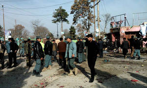 Photo - Afghan police forces and civilians inspect the site of a suicide attack in Maymana, capital of Faryab province, Afghanistan, Tuesday, March 18, 2014.  A suicide bomber riding a rickshaw blew himself up outside a checkpoint at a market in northern Afghanistan on Tuesday, killing at least 13 civilians, officials said, in the latest attack in the countdown to presidential elections to be held in less than three weeks. (AP Photo)