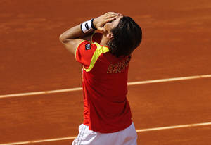 Photo -   Spain's David Ferrer celebrates winning against John Isner of the US at the Davis Cup World Group semifinal tennis match in Gijon, northern Spain, Sunday, Sept. 16, 2012. Ferrer won 6-7, 6-3, 6-4, 6-2. (AP Photo/Alvaro Barrientos)