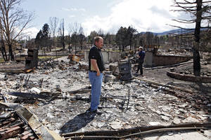 Photo -   Members of FEMA and the Small Business administration look at a burned home in Colorado Springs, Colo., on Monday, July 9, 2012. Members of FEMA, the SBA and Colorado's Disaster Office assessed damages in the area burned by the Waldo Canyon wildfire. (AP Photo/Ed Andrieski)