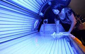 Photo - FILE - In this April 2, 2014 file photo, Teresa Lynch, owner of Dynamic Tanning in DeKalb, Ill., wipes down a tanning bed. Tanning beds and sun lamps will carry new warnings that they should not be used by anyone under age 18, under a government action Thursday, May 29, 2014, aimed at reducing rising rates of skin cancer linked to the radiation-emitting devices. (AP Photo/Daily Chronicle, Monica Maschak, File)  MANDATORY CREDIT