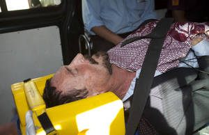 photo - Software company founder John McAfee lies on a gurney inside an ambulance, to be transferred from an immigration detention center to a hospital, in Guatemala City, Thursday, Dec. 6, 2012 . He was examined by a doctor at the detention center, who said that McAfee's heart and blood pressure were normal, but nonetheless was being moved to a hospital after McAfee was found lying on the floor in the room where he was being detained. McAfee who fled Belize was denied political asylum in Guatemala on Thursday and police in Belize said they expected him to be flown back soon for questioning about the killing of a fellow American expatriate.(AP Photo/Moises Castillo)