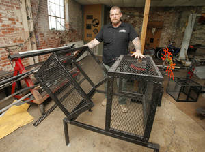 Photo - Nathan White, owner of Ace's Fabrication and Design, displays a finished Clamshell Cage. The cages are designed to protect air conditioning units from theft. Photo by Paul B. Southerland, The Oklahoman