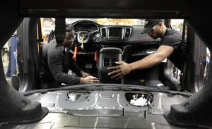 Photo -   Assembly line workers build a 2015 Chrysler 200 automobile at the Sterling Heights Assembly Plant in Sterling Heights, Mich.  AP Photo  <strong>Paul Sancya -  AP </strong>