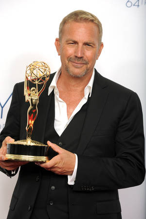 "Photo -   Actor Kevin Costner, winner of the Emmy for outstanding lead actor in a miniseries or movie for ""Hatfields & McCoys,"" poses backstage at the 64th Primetime Emmy Awards at the Nokia Theatre on Sunday, Sept. 23, 2012, in Los Angeles. (Photo by Jordan Strauss/Invision/AP)"