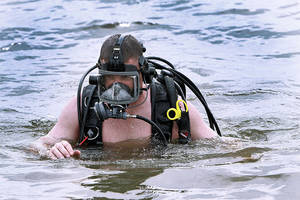 Photo - Chris Lunz with the Connecticut State Police works on placing  flotation bags on a submerged car in Lake Arcadia,   Wednesday, June 13, 2012. Edmond police are holding an underwater explosive recovery specialist course. Photo By David McDaniel, The Oklahoman