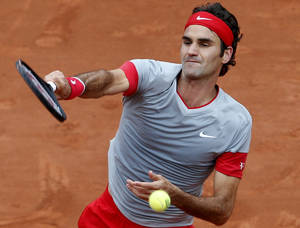 Photo - Switzerland's Roger Federer smashes the ball to Argentina's Diego Sebastian Schwartzman during the second round match of  the French Open tennis tournament at the Roland Garros stadium, in Paris, France, Wednesday, May 28, 2014. Federer won 6-3, 6-4, 6-4. (AP Photo/Darko Vojinovic)