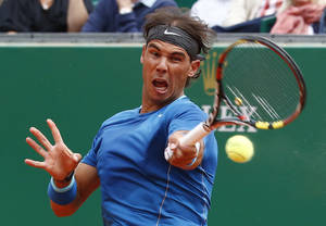 Photo - Rafael Nadal of Spain returns the ball to Teymuraz Gabashvili of Russia during their match of the Monte Carlo Tennis Masters tournament in Monaco, Wednesday, April 16, 2014. Nadal won 6-4 6-1. (AP Photo/Michel Euler)