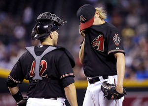 Photo - Arizona Diamondbacks pitcher Bronson Arroyo, right, wipes his face as he talks with catcher Miguel Montero during the fourth inning of a baseball game against the New York Mets on Tuesday, April 15, 2014, in Phoenix. (AP Photo/Matt York)
