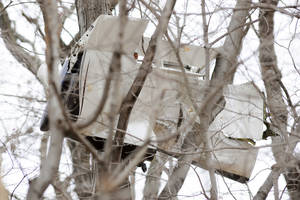 Photo -   A piece of a small plane hangs from a tree located between Hilltop Circle and James Street near Interstate 287 where the plane crashed forcing the police to close all lanes of the highway to conduct their investigation, Tuesday, Dec. 20, 2011 in Harding Township, N.J. (AP Photo/Joe Epstein)