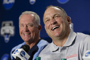 Photo - FILE - In this June 14, 2013, file photo, North Carolina State coach Elliott Avent, right, laughs with North Carolina coach Mike Fox during a news conference in Omaha, Neb. The programs separated by about a 30-minute drive enter the 2014 season among the nation's top-ranked teams--and they'd love to have another rendezvous on the sport's biggest stage. (AP Photo/Nati Harnik, File)