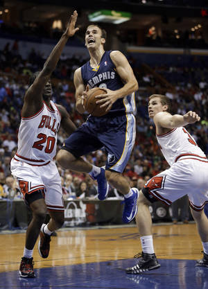 Photo - Memphis Grizzlies' Nick Calathes, center, heads to the basket past Chicago Bulls' Tony Snell, left, and Erik Murphy during the first half of an NBA preseason basketball game Monday, Oct. 7, 2013, in St. Louis. (AP Photo/Jeff Roberson)