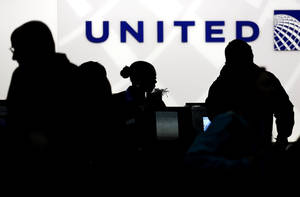 Photo - FILE - In this Saturday, Dec. 21, 2013, file photo, travelers check in at the United Airlines ticket counter at Terminal 1 in O'Hare International Airport in Chicago. Starting March 2015, elite members of United's MileagePlus will earn between 7 and 11 miles for every dollar they spend on tickets, not counting taxes. Regular members, those who fly less than 25,000 miles and spend less than $2,500 a year, will get 5 miles per dollar toward free travel. (AP Photo/Nam Y. Huh, File)