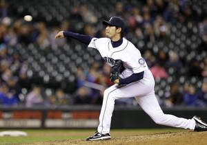 Photo - Seattle Mariners starting pitcher Hisashi Iwakuma throws against the Kansas City Royals in the eighth inning of a baseball game Wednesday, Sept. 25, 2013, in Seattle. The Mariners won 6-0. (AP Photo/Elaine Thompson)