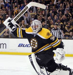 Photo -   Boston Bruins' Tim Thomas celebrates after blocking the shot by Buffalo Sabres' Jason Pominville, giving the Bruins a 4-3 win, in a shootout during an NHL hockey game in Boston, Saturday, April 7, 2012. (AP Photo/Michael Dwyer)