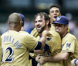 Photo - Milwaukee Brewers congratulate Sean Halton, center, after he hit a game-winning solo home run in the bottom of the ninth inning of a baseball game against the Cincinnati Reds, Sunday, Sept. 15, 2013, in Milwaukee. The Brewers won 6-5. (AP Photo/Andy Manis)