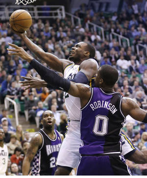 Photo - Utah Jazz's Paul Millsap, left, lays the ball as Sacramento Kings' Thomas Robinson (0) defends in the second half during an NBA basketball game Monday, Feb. 4, 2013, in Salt Lake City. The Jazz defeated the Kings 98-91 in overtime. (AP Photo/Rick Bowmer)