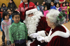 Photo - This photo taken Wednesday, Dec. 11, 2013, in Kwethluk, Alaska, shows children at the school standing in line to Santa and Mrs. Claus. The visit is part of the Alaska National Guard's Operation Santa Claus, which visits several remote Alaska Native villages each year.  (AP Photo/Mark Thiessen)