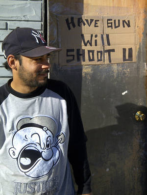 photo -   Alex Ocasio, 37, stands next to the sign he posted on the door of his first floor apartment on Rockaway Beach Boulevard in the Queens borough of New York, Tuesday, Nov. 6, 2012 in New York. Ocasio plans to ride out the Noreaster at his first-floor apartment even after Sandy flooded his street with neck-high water and someone tried to break in afterward. (AP Photo/Tom Hays)  