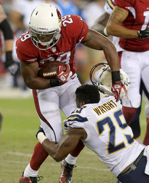 Photo - San Diego Chargers defensive back William Middleton, right, loses his helmet as he tackles Arizona Cardinals running back Alfonso Smith, left, during the first half of a preseason NFL football game, Saturday, Aug. 24, 2013, in Glendale, Ariz. (AP Photo/Rick Scuteri)