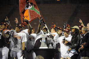 Photo - Virginia Tech players take the stage with their trophy after defeating  Rutgers 13-10 in overtime of an NCAA college football Russell Athletic Bowl game on Friday, Dec. 28, 2012, in Orlando, Fla. (AP Photo/Brian Blanco)