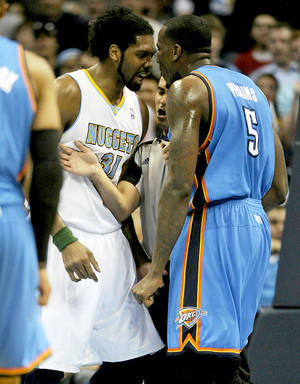 Photo - Nuggets center Nene, left, and Thunder center Kendrick Perkins are separated by a referee during their April 5 game at the Pepsi Center in Denver. PHOTO BY AARON ONTIVEROZ, THE DENVER POST