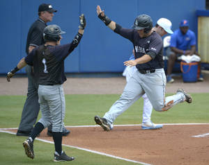 Photo - Long Beach State's Garrett Hampson (1) and Ino Patron, right, congratulate each other after both scored off a single by Michael Hill during the seventh inning of an NCAA college baseball regional tournament game against North Carolina in Gainesville, Fla., Monday, June 2, 2014. Long Beach State won 12-5.(AP Photo/Phelan M. Ebenhack)