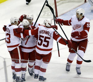 Photo - Red Wings players celebrate a goal by Johan Franzen, far left, of Sweden, during the third period of an NHL hockey game against the New Jersey Devils, Friday, Dec. 6, 2013, in Newark, N.J. (AP Photo/Julio Cortez)