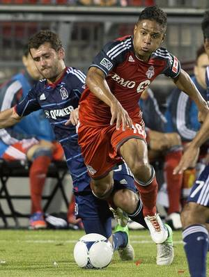 photo -   Toronto FC&#039;s Quincy Amarikwa tries to cut between Chicago Fire&#039;s Gonzalo Segares, left, during the first half of an MLS soccer game in Toronto on Wednesday, Sept. 12, 2012. (AP Photo/The Canadian Press, Chris Young)  