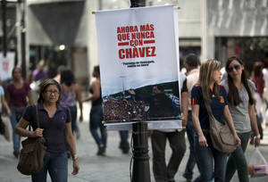 "Photo - A banner that reads in Spanish ""Now more than ever with Chavez"" on a street pole in Caracas, Venezuela, Saturday, Dec. 15, 2012. Hugo Chavez's cancer has upended politics in Venezuela, transforming Sunday's nationwide elections for state governors and legislators into a test of his legacy that could chart the country's future in the uncertain months ahead. (AP Photo/Ariana Cubillos)"