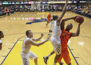 Photo - Oklahoma State's Le'Bryan Nash (2) is fouled by West Virginia's Gary Browne (14) during the first half of an NCAA college basketball game in Morgantown, W.Va., on Saturday, Feb. 23, 2013. (AP Photo/David Smith)