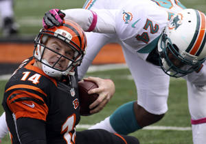 Photo -   Cincinnati Bengals quarterback Andy Dalton (14) is tackled by Miami Dolphins cornerback Sean Smith (24) after a short gain in the second half of an NFL football game on Sunday, Oct. 7, 2012, in Cincinnati. Miami won 17-13. (AP Photo/Tom Uhlman)