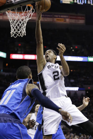 Photo - San Antonio Spurs' Tim Duncan (21) shoots over Dallas Mavericks' Monta Ellis (11) during the first quarter of Game 1 of the opening-round NBA basketball playoff series on Sunday, April 20, 2014, in San Antonio. (AP Photo/Eric Gay)