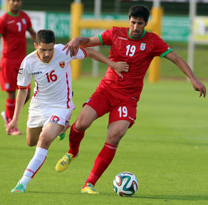 Photo - Iran's Hashem Beikzadeh, right, challenges for a ball with Miroie Jovanovic, left, of Montenegro during a friendly soccer match between Iran and Montenegro, in Hartberg, Austria, Monday, May 26, 2014. (AP Photo/Ronald Zak)