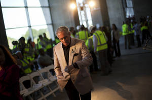 In this May 16, 2016, file photo, Atlanta Falcons owner Arthur Blank checks his watch before the start of a press event at the team's new stadium currently under construction in Atlanta. The 2019 Super Bowl is scheduled to be played at the new stadium.  (AP Photo/David Goldman, File)