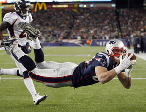 photo - New England Patriots tight end Rob Gronkowski (87) catches a 10-yard touchdown pass while being defended by Denver Broncos cornerback Andre' Goodman (21) during the first half of an NFL divisional playoff football game Saturday, Jan. 14, 2012, in Foxborough, Mass. (AP Photo/Charles Krupa)  ORG XMIT: FBO118