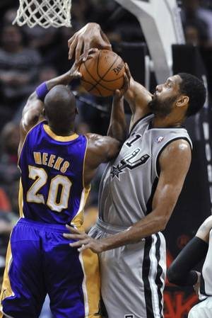 Photo - San Antonio Spurs forward Tim Duncan blocks a shot attempt by Los Angeles Lakers guard Jodie Meeks during the first half of an NBA basketball game Friday, March 14, 2014, in San Antonio. (AP Photo/Bahram Mark Sobhani)