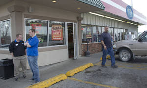 photo - An unidentified customer walks out of the  Trex Mart convenience store, right, while manager Chris Nauerz, left, and son of the owner Baron Hartell stand outside, in Dearborn, Mo., Thursday, Nov. 29, 2012. Lottery officials confirmed Thursday that one of two winning Powerball tickets sold before Wednesday's drawing was bought at a Trex Mart convenience store in Dearborn. (AP Photo/Orlin Wagner)