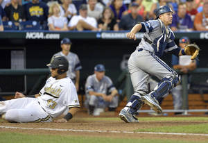 Photo - Vanderbilt's Zander Wiel, left, slides home on a sacrifice fly ball by John Norwood, as UC Irvine catcher Jerry McClanahan, right, waits for the ball, in the fifth inning of an NCAA baseball College World Series game in Omaha, Neb., Monday, June 16, 2014. (AP Photo/Ted Kirk)