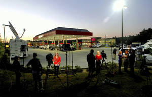 Photo - The media work at the Murphy Express gas station Thursday morning, Sept. 19, 2013, in Lexington, S.C., after the announcement that the winning Powerball ticket was sold here. Lottery officials said early Thursday that the ticket was sold at the Murphy USA station. The winning numbers drawn Wednesday night were 7-10-22-32-35 with the Powerball of 19. (AP Photo/The State, Tim Dominick)