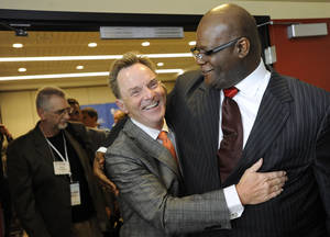 Photo - The Rev. Ronnie Floyd, center, of Cross Church in northwest Arkansas, hugs The Rev. Dwight McKissic, right, of Cornerstone Baptist Church in Arlington, Texas, after Floyd was elected the new president of the Southern Baptist Convention during its annual meeting Tuesday, June 10, 2014, in Baltimore. Floyd received 52 percent of votes cast by delegates to the annual meeting of the nation's largest Protestant denomination. (AP Photo/Steve Ruark)