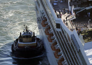 photo - In this aerial photo, the cruise ship Carnival Triumph is towed into Mobile Bay, Ala. Thursday, Feb. 14, 2013. The ship with more than 4,200 passengers and crew members has been idled for nearly a week in the Gulf of Mexico following an engine room fire. (AP Photo/Gerald Herbert)