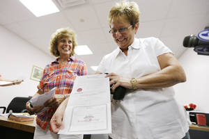 Photo - Ellen Toplin, right, and Charlene Kurland pose for photographs with their marriage license at a Montgomery County office despite a state law banning such unions, Wednesday, July 24, 2013, in Norristown, Pa.  The chairman of the Montgomery County commissioners, Democrat Josh Shapiro, said he supports same-sex marriage and was ready for the county to defend the stance in court.   (AP Photo/Matt Rourke)
