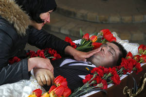 Photo - Elena, the widow of slain council man Volodymr Rybak caresses the face of her husband as his body lays in the coffin prior to his funeral after his body was found on Tuesday after his alleged abduction by pro-Russian insurgents in the eastern city of Horlivka, Ukraine, Thursday, April 24, 2014. (AP Photo/Sergei Grits)